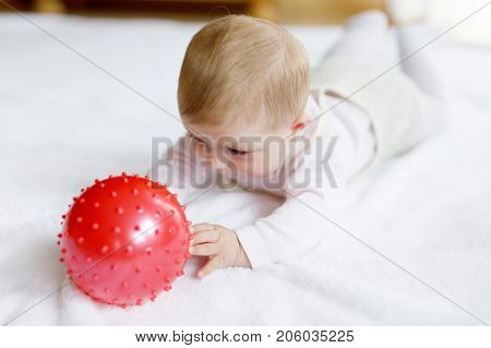 Cute baby playing with red gum ball. New born child, little girl having fun, grabbing and crawling. Family, new life, childhood, beginning concept. Baby learning grab