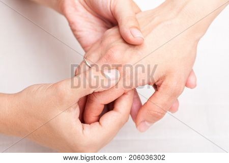 Young woman's finger being manipulated by osteopathic manual therapist or physician