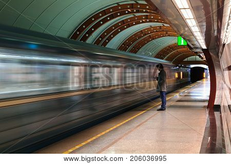 Lonely young man with smartphone shot from profile at subway station with blurry moving train in background