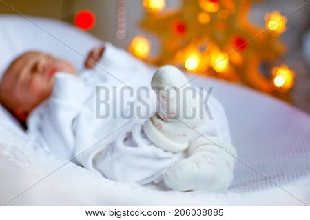 One week old newborn baby sleeping near Christmas tree with colorful garland lights on background. Closeup of cute child, little baby girl, focus on feet. Family, Xmas, birth, new life