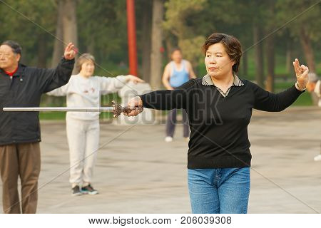 BEIJING, CHINA - MAY 01, 2009: Unidentified lady practices traditional gymnastics with a sword in Jingshan Park in Beijing, China.