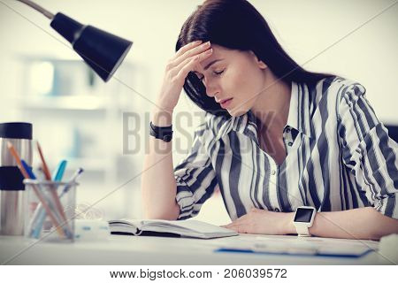 Feeling tired. Unhappy gloomy good looking woman sitting at the table and holding her forehead while feeling tired