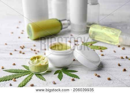 Cosmetics with hemp extract on white wooden background