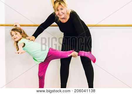 Instructor helping girl on ballet barre toned image