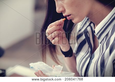 My treatment. Pleasant nice young woman holding a plastic box and eating a pill while taking her medicine