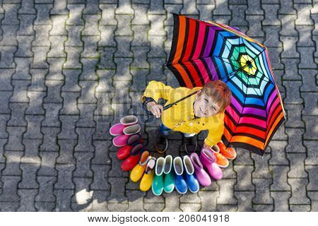 Little kid boy and group of colorful rain boots. Blond child standing under umbrella. Close-up of schoolkid and different rubber boots from high angle.Footwear for rainy fall. Concept of bright autumn