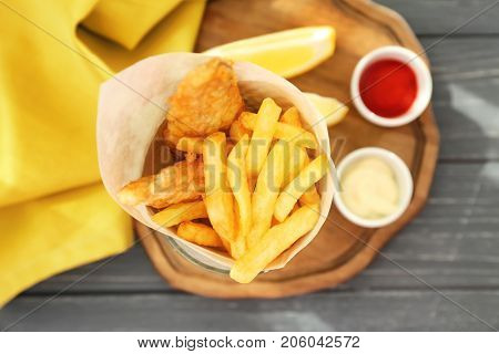 Tasty fried fish and chips rolled in paper on wooden table