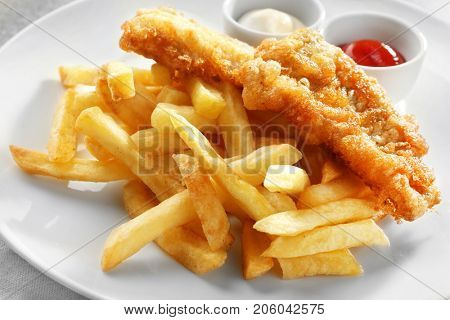 Tasty fried fish, chips and sauces on plate, closeup