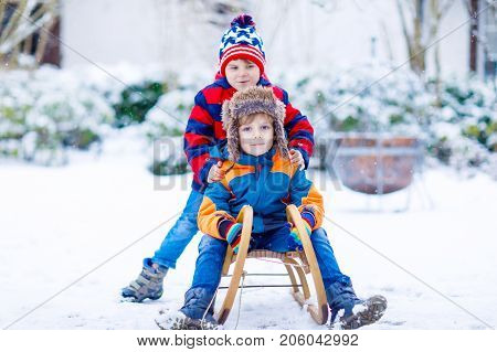 Two kid boys enjoying sleigh ride during snowfall. Children sledding on snow. siblings riding a sledge. twins play outdoors. Friends sled in snowy winter park. Active fun for family Christmas vacation.