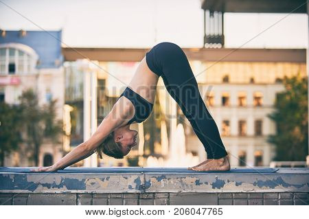 Beautiful sporty fit yogini woman practices yoga asana downward facing dog in the city