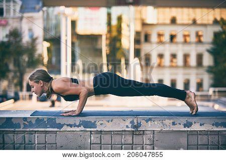 Beautiful sporty fit yogini woman practices yoga asana Chaturanga Dandasana - four limbed staff pose in the city