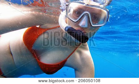 Woman dive underwater in snorkeling diving mask and snorkel in the clear blue sea water.