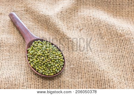 The background image of green beans in the wooden ladle on sackcloth .