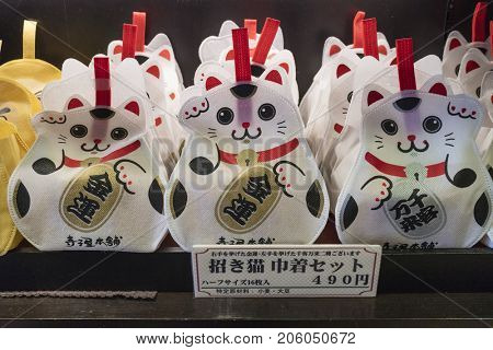 Kyoto, Japan -  May 17, 2017:  Traditional happy cat, maneki-neko, sac filled with sweets on the Nishiki market as a souvenir