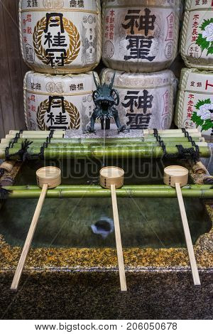 Kyoto, Japan - May 16, 2017: Row of ladles at a purificaton basin with a dragon gargoyle near the shinto temple