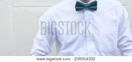 Stylish groom in white shirt with green bow tie
