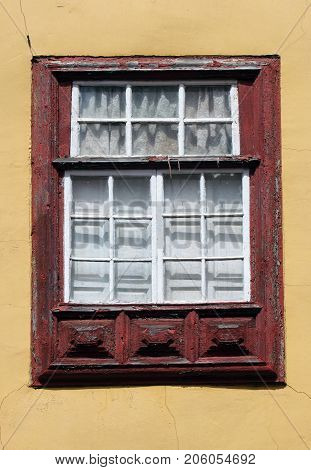 old red painted window frame with white borers on small panes of glass internal white shutters and yellow cracked wall