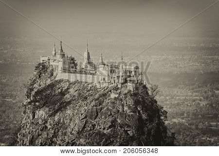 Famous buddhist temple on the summit of Taung Kalat volcano near Mt. Popa. 777 stairs have to be climbed barefoot along with monkeys to reach the top, end of pilgrimage. Myanmar. Toned in sepia