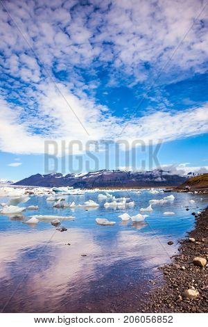 Clouds reflected in the water of lagoon. The ice floes and cirrocumulus clouds of lagoon Jokulsarlon, Iceland. The concept of northern extreme tourism