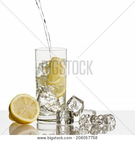 glass full of fresh water with lemon and ice cubes on background