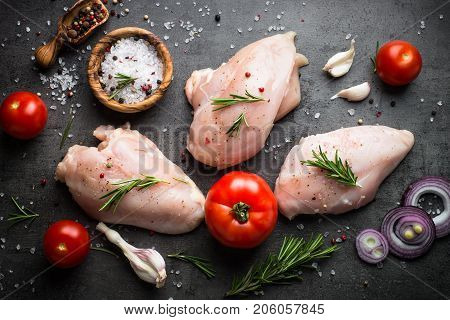 Raw chicken fillet with sea salt pepper and rosemary on black. Food background cooking ingredients. Fresh meat. Chicken breast.