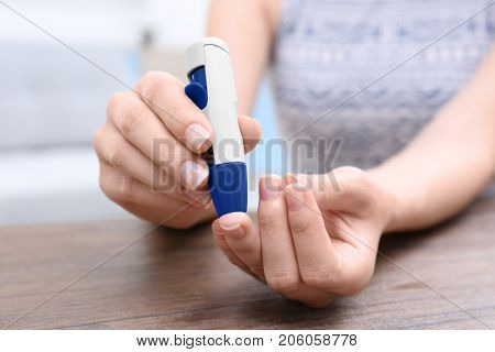 Woman taking blood sample with lancet pen indoors