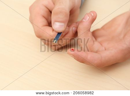 Hands of man using test strip for blood sugar monitoring. Diabetes concept