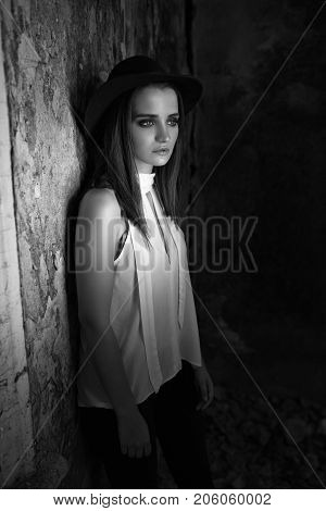 A girl in a white blouse, a black hat. with tare destroyed building. Helouin. Black and white photo