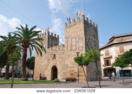 MAJORCA, SPAIN - SEPTEMBER 8, 2017: The medieval Xara Gate (Portal del Moll) in the Old Town area of Alcudia on the Spanish island of Majorca. The gate once formed a defence for the walled town.