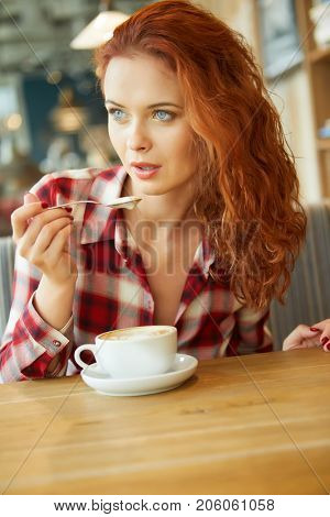 Beautiful red-haired woman in cafe. Blogger work concept