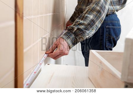 Contractor measuring a kitchen with tape measure