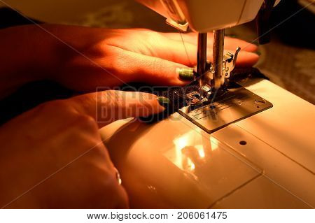 Female hands on sewing machine. Modern sewing process. Tailoring Process - Women's hands behind her sewing