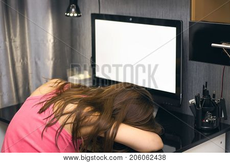 Girl was asleep sitting at the computer with blank screen monitor. Lack of time concept tiredness concept boredom.