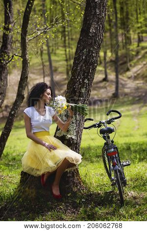 Beautiful woman with a bunch of snowdrops and a bicycle resting in the forest