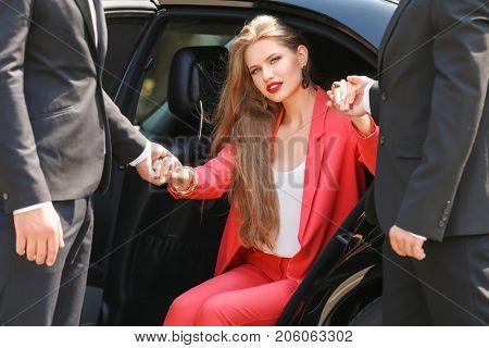 Bodyguards helping young businesswoman to get out of car