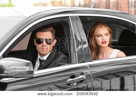 Young celebrity with bodyguard in modern car