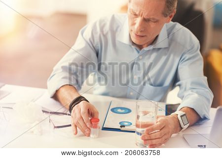It wil help. Cheerless professionla mature male office worker sitting at the table and going to take medicines while sitting in the office