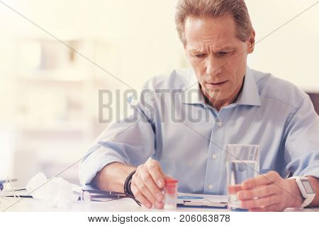 Take your dose. Moody sick mature man sitting in the office and holding a glass of water while going to take pills