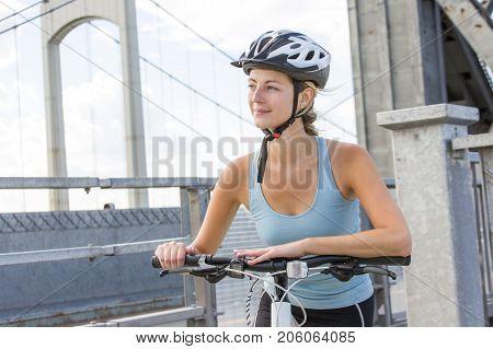A Young and beautiful Woman Riding Bike outside