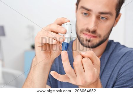 Man taking blood sample with lancet pen indoors. Diabetes concept