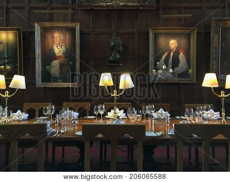OXFORD, UK - MAY 22, 2017: Table prepared for dinner at The Great Hall of Christ Church, University of Oxford. It has been used as a prototype for the Hall at Harry Potter's Hogwarts school.
