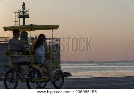 Rimini Italy - July 31 2017: Four-wheeled bicycle at the harbor at sunset