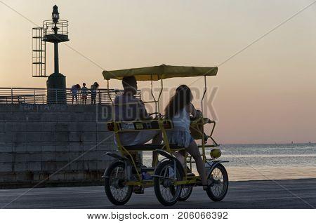 Rimini Italy - July 31 2017: Four-wheeled bicycle at the marina at sunset