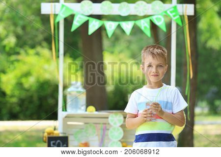 Cute little boy with glass near lemonade stand in park