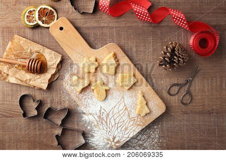 Christmas composition with raw cookies and cutters on wooden table