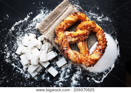 Delicious Fresh Bavarian pretzel on dark background with flour. Sweet pretzels with powdered sugar macro. Beautiful delicious puff pastry