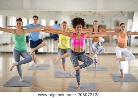 Group of attractive women doing yoga and balance exercises inside