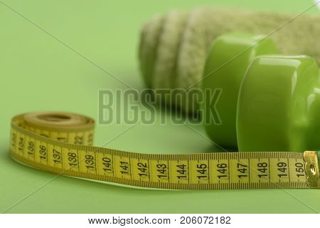 Dumbbells In Green Color, Twisted Measure Tape And Towel