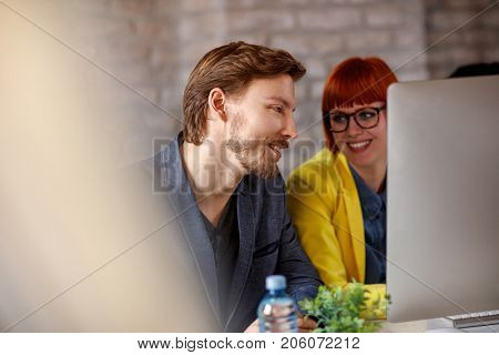 Businessman with businesswoman together at job consults about business on computer