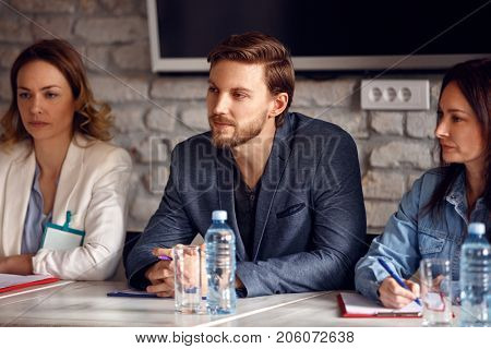 Serious man with two female colleagues in commission for employment in company